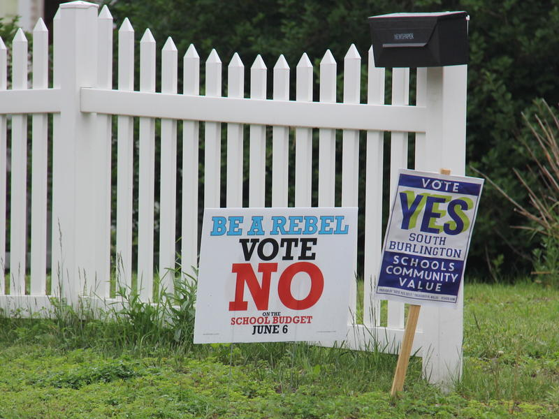 A sign encouraging voters to reject the school budget and another to approve it on a lawn in South Burlington. The decision to change the school mascot name has loomed over the budget debate.