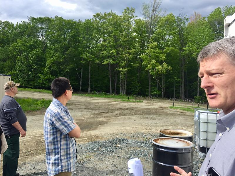 Jim Wieck, far right, a hydrogeologist and senior project manager overseeing the Rennie Farm cleanup, talks to residents about the pump and treat system at the former Dartmouth College burial site.