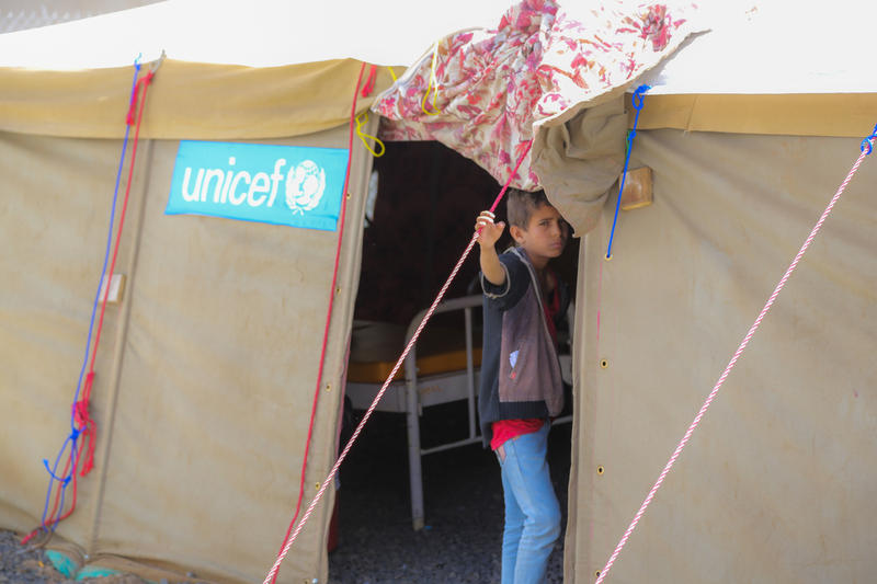 A child stands by the door of a UNICEF medical tent in Yemen. In the last few weeks, there have been over 100,000 suspected cases of cholera in Yemen and that number is expected to rise.