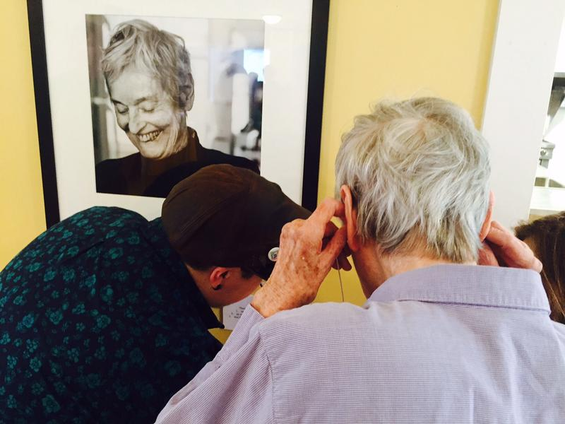 Eva Mondon, in foreground, listens to a recording she made about the Andrew's Inn at an exhibit at Next Stage Arts in Putney. A portrait of Mondon hangs on the wall.