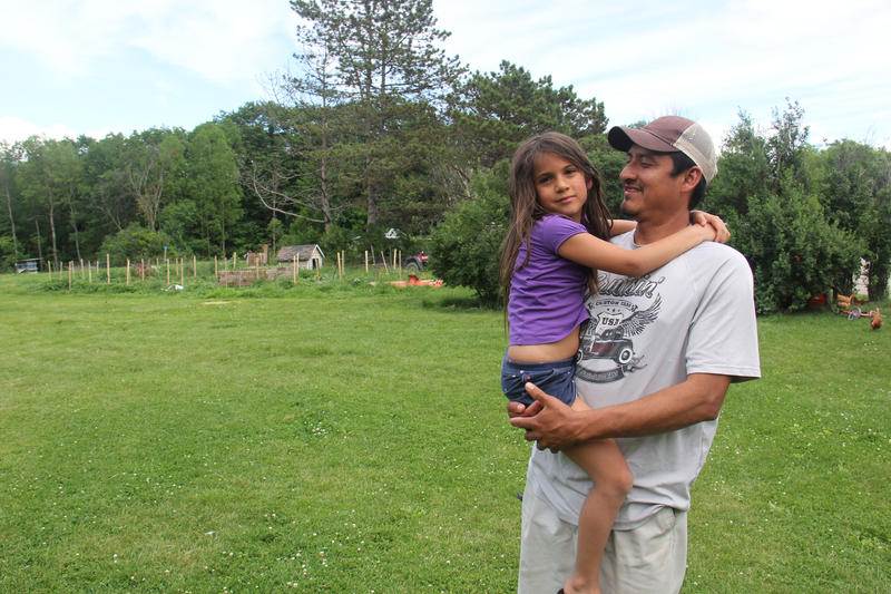 Juan De La Cruz comforts his youngest daughter, Isabella, at their home in Vergennes.