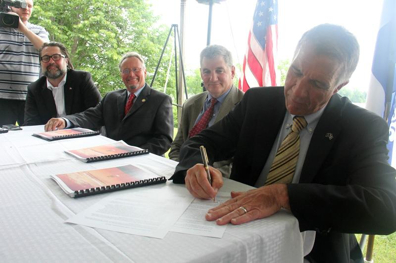 As top environmental officials from Quebec and New York looked on, Gov. Phil Scott signed a letter committing to reduce pollution in Lake Champlain as part of an inter-state and international effort.