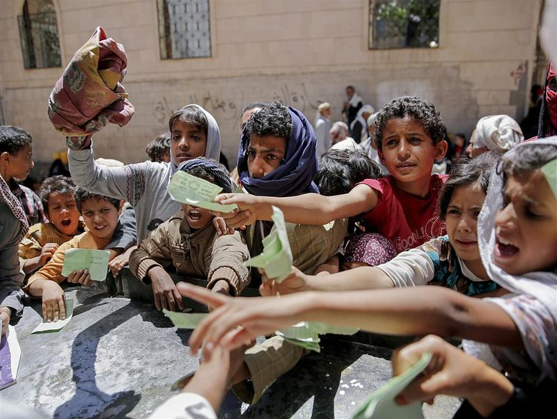 Yemenis present documents in order to receive food rations provided by a local charity, in Sanaa, Yemen, Thursday, April, 13, 2017. A stalemated war with Saudi Arabia has pushed the Arab world's poorest country to the brink of famine.