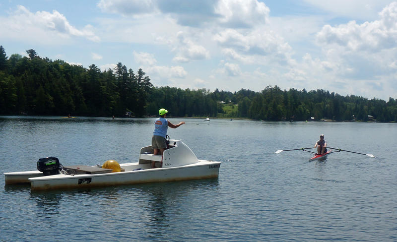 A Craftsbury Outdoor Center rowing coach instructs a camper on Great Hosmer Pond from a motorized coaching launch.