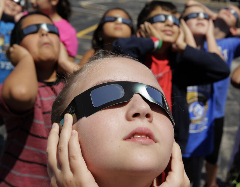 Elementary school students in Kansas City, Mo., practice with their eclipse glasses. This post has what you need to monitor the eclipse from here in Vermont.
