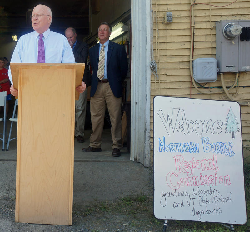 Sen. Patrick Leahy speaks to a crowd at a barn along Route 15 in Hardwick Thursday, as Gov. Phil Scott looks on. Leahy and Scott were in Hardwick to announce the recipients of Northern Border Regional Commission grants.