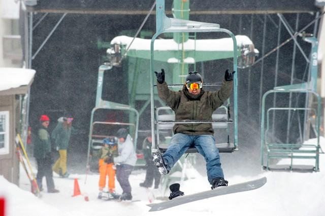 One of the first riders of the 2016-17 season hops on the chairlift at Bolton Valley. Bolton Valley is one of the Vermont ski resorts that uses the J-1 visa program.