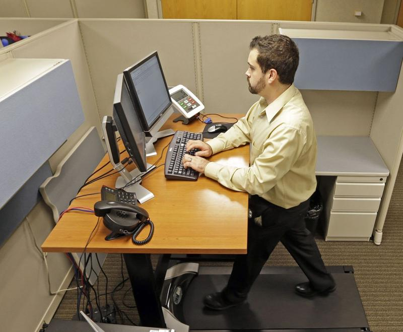 In this 2013 photo, an employee of Brown & Brown Insurances uses a treadmill desk