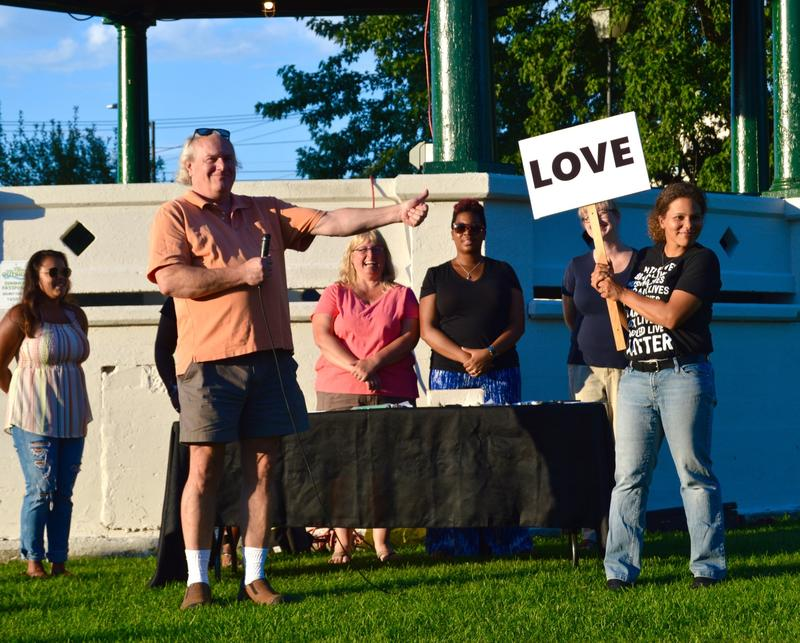 David Liebtag, of Chester, handed his sign to Tabitha Pohl-Moore, President of the Rutland Chapter of the NAACP during a rally Monday night in Rutland.  It was held to condemn racist violence that erupted in Charlottesville, Virginia on Saturday.