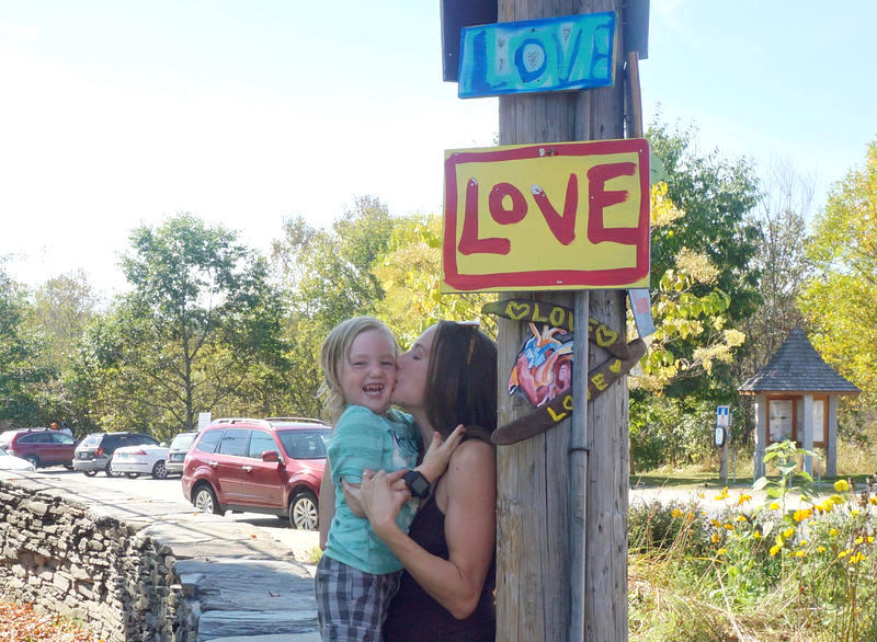 Jacquelyn Ripley gives her son Landen a smooch under the Plainfield 'love' signs. The anonymous signs have drawn strong reactions from some townspeople.