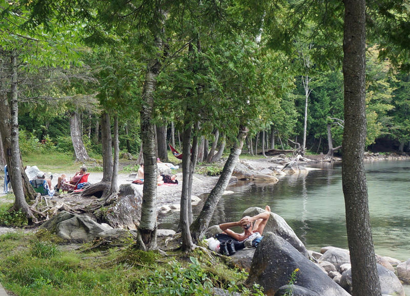 Beachgoers enjoy a summer day at Lake Willoughby's clothing-optional Southwest Cove. Many regulars here feel changes proposed by the state could spoil this secluded getaway.