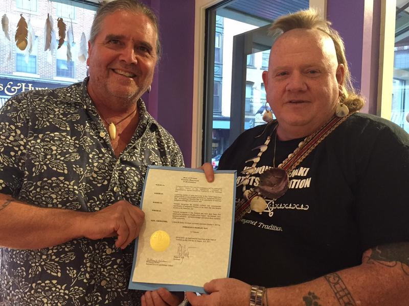Rich Holschuh, left, of Brattleboro and Roger Longtoe Sheehan, who is the Chief of the Elnu Tribe of the Abenaki, hold Governor Phil Scott's proclamation naming October 9 Indigenous Peoples' Day in Vermont.