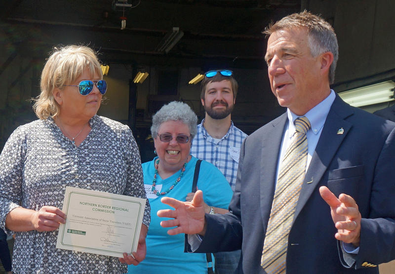 After presenting a grant award to Cindy Locke of VAST on Aug. 10, Gov. Phil Scott recounts a snowmobile trip on the Lamoille Valley Rail Trail when his security team rigged his sled to run only at low speeds, putting a governor on the governor.