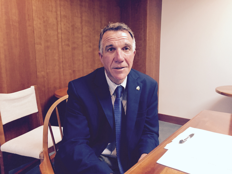 Gov. Phil Scott sitting at a table with papers on it, looking at the camera.