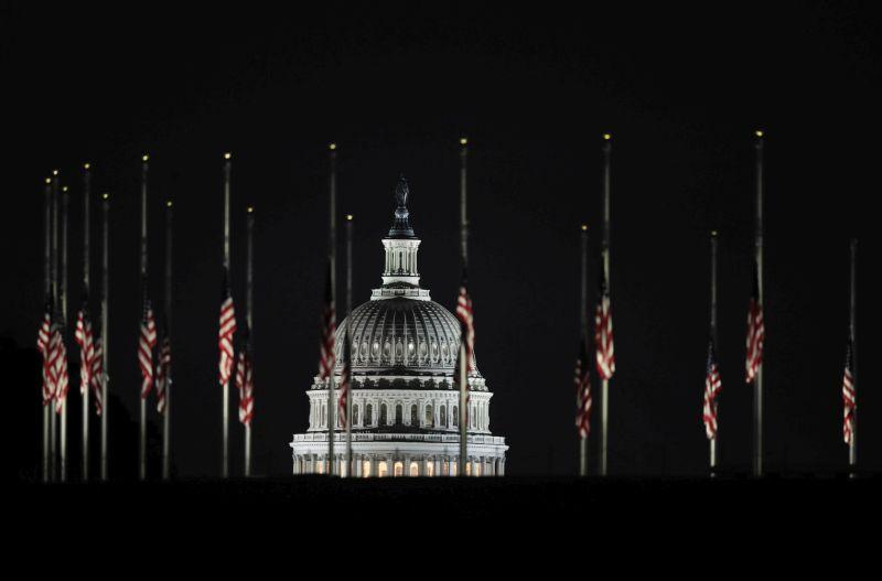 The U.S. Capitol dome backdrops a column of American flags standing at half-staff at dawn on Tuesday, Oct. 3, 2017, at the foot of the Washington Monument on the National Mall in Washington.
