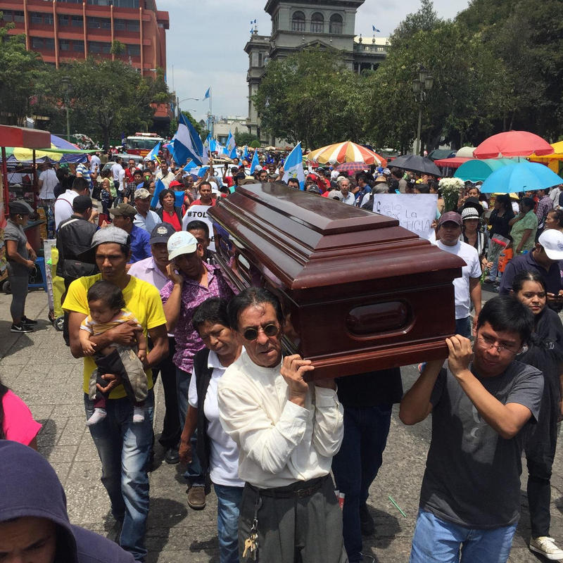 Guatemalan citizens carry an empty coffin in front of Guatemala's National Palace. The coffin symbolizes what demonstrators called the death of democracy following their president's attempt to expel the head of the CICIG.