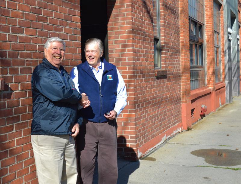 Joe Giancola, a prominent Rutland developer shakes hands with R. John Mitchell in front of former headquarters of the Rutland Herald. The Mitchell family owned the newspaper and the building that housed it for decades.
