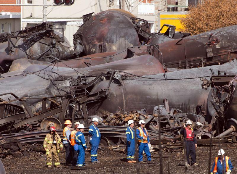 In this July 6, 2013 file photo, workers stand before mangled tanker cars at the crash site of the train derailment and fire in Lac-Megantic, Quebec, Canada. Three railroad workers are on trial this week in Quebec for criminal neglience.