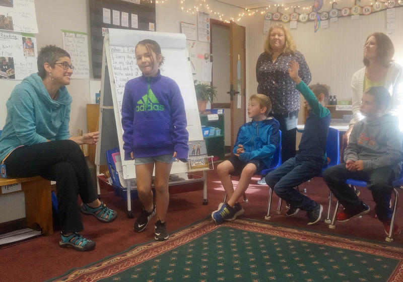 Second graders in Karen Anderson's classroom work with Reading Specialist Donna Cullivan, learning a poem from a big sheet of paper on an easel. Their hotel room classroom has a kitchenette and bathroom, but no chalkboard or whiteboard on the wall.