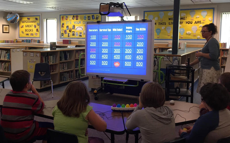 "Fourth grade students at Northfield Elementary School played a Jeopardy!-style game, led by school librarian Nanette Smith, that featured questions about Peter Brown's novel ""The Wild Robot."""