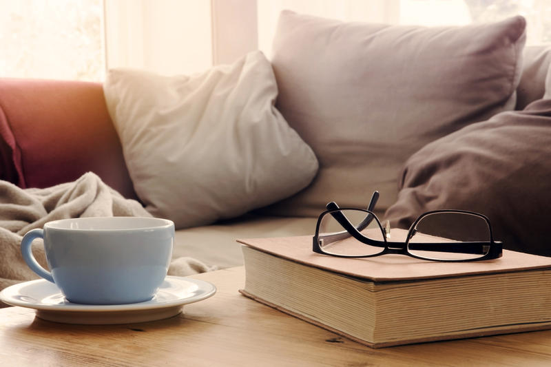 Glasses, a book and a mug sit on a wood table in front of a couch with pillows.