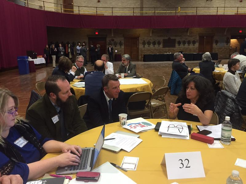 Gov. Phil Scott, in center, listens to Vermont educators talk about education spending at a summit at Norwich University on Monday.