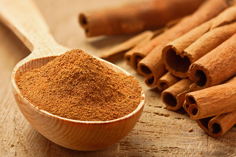 Ground cinnamon in a spoon and cinnamon sticks on a table.