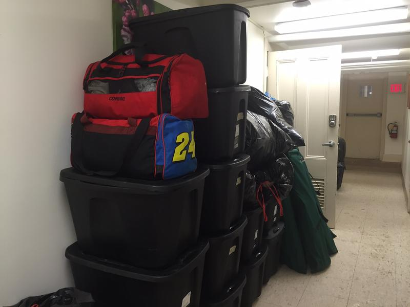 A pile of bags and other personal belongings in a church basement.