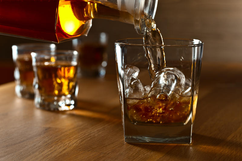 Whiskey bottle pouring into a glass with ice.