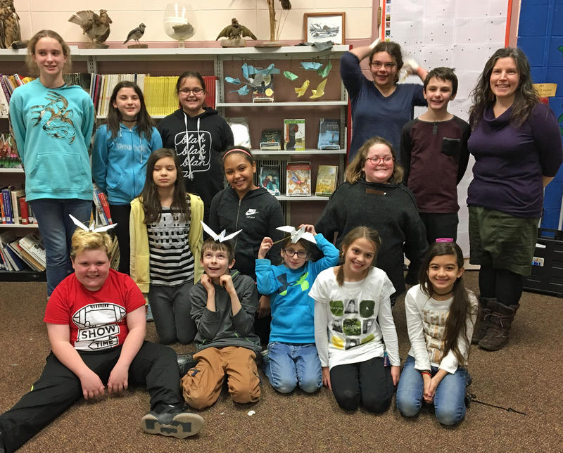 "Students at Dover Elementary School gathered in the library to discuss Kelly Barnhill's novel ""The Girl Who Drank the Moon"" and posed with the paper birds they made."