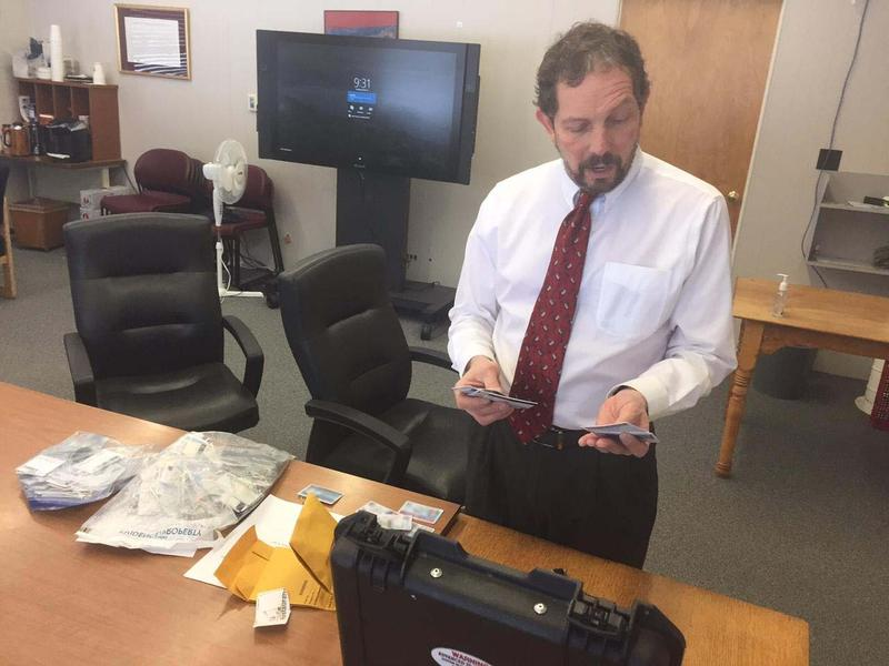 Department of Liquor Control Deputy Commissioner Gary Kessler looks through some of the fake IDs the state collected using a new high-tech scanner.