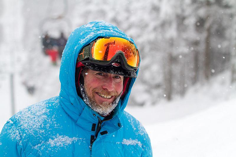 John Egan, a private ski instructor at Sugarbush Resort, outside on a snowy day wearing a blue coat and goggles.