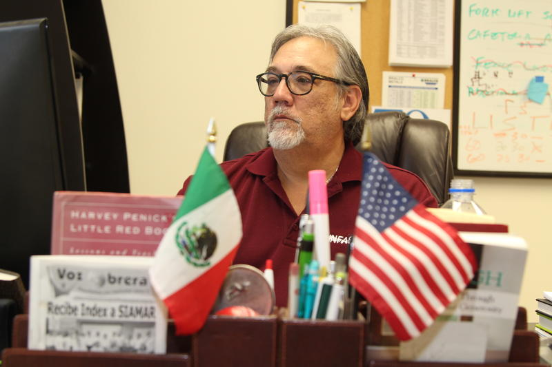 Mike Myers runs a U.S.-owned mass assembly factory, or maquila, in Reynosa, Mexico. Myers is seated at a desk with a Mexican and American flag in foreground.