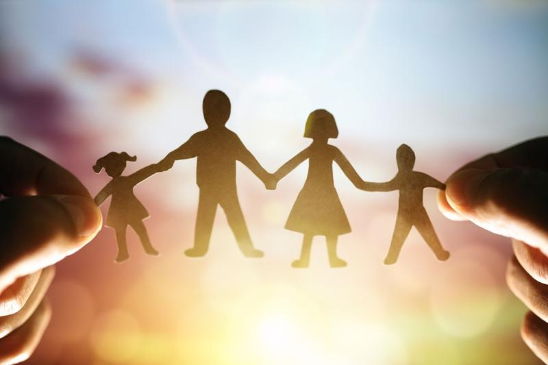 a paper chain cutout of a family held up by two hands with a sunset in the background.