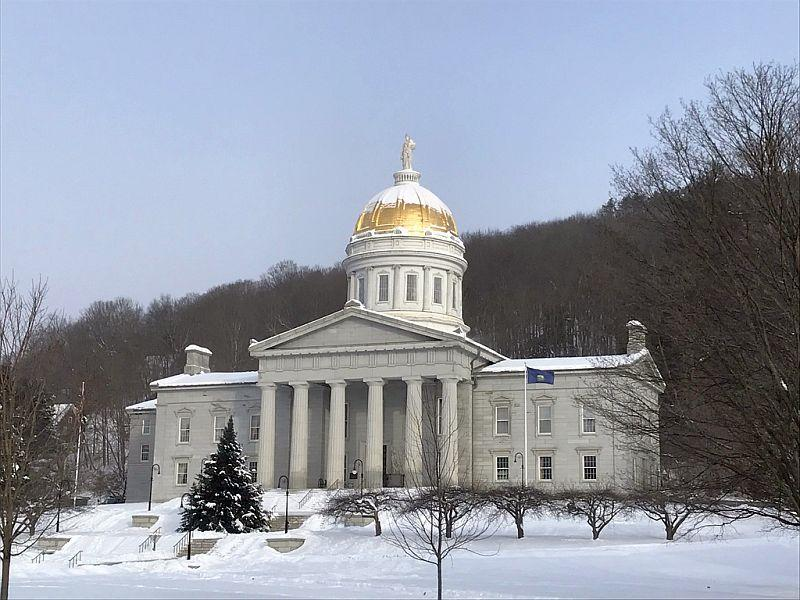The Vermont Statehouse with snow around it.