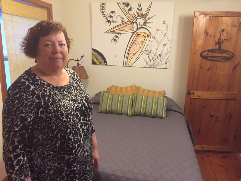 Nanci Leitch stands in the bedroom in her house in Guilford. There's a bed and a painting on the wall.