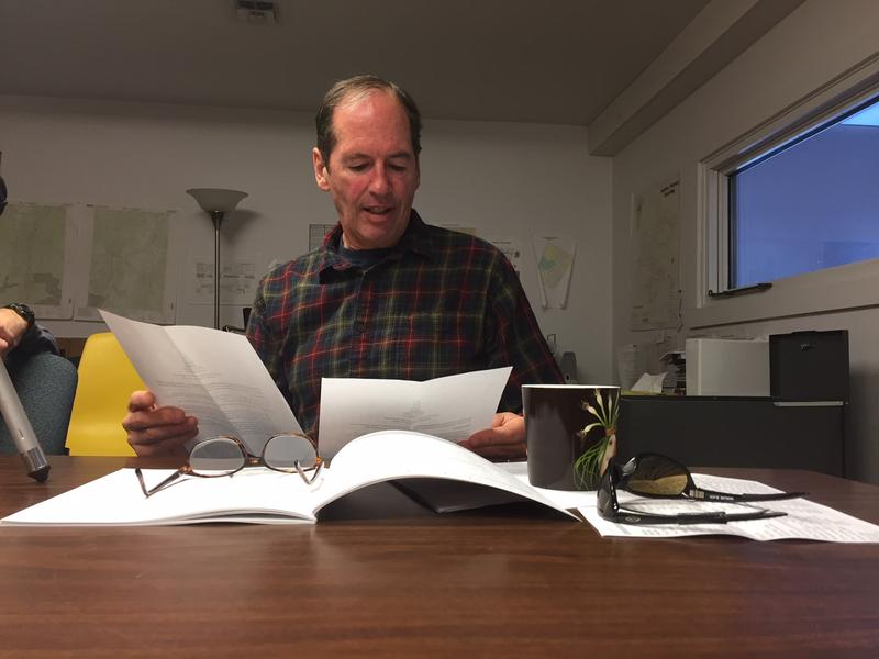 Jared Cadwell, the Fayston selectboard chairman, holds papers at a desk and looks over the town's Town Meeting Day warning in the town's municpal building.