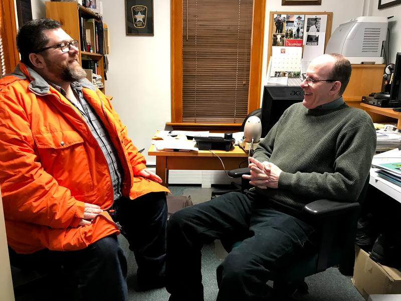 Patrick Warn talks in an office to Lamoille County Sheriff Roger Marcoux.