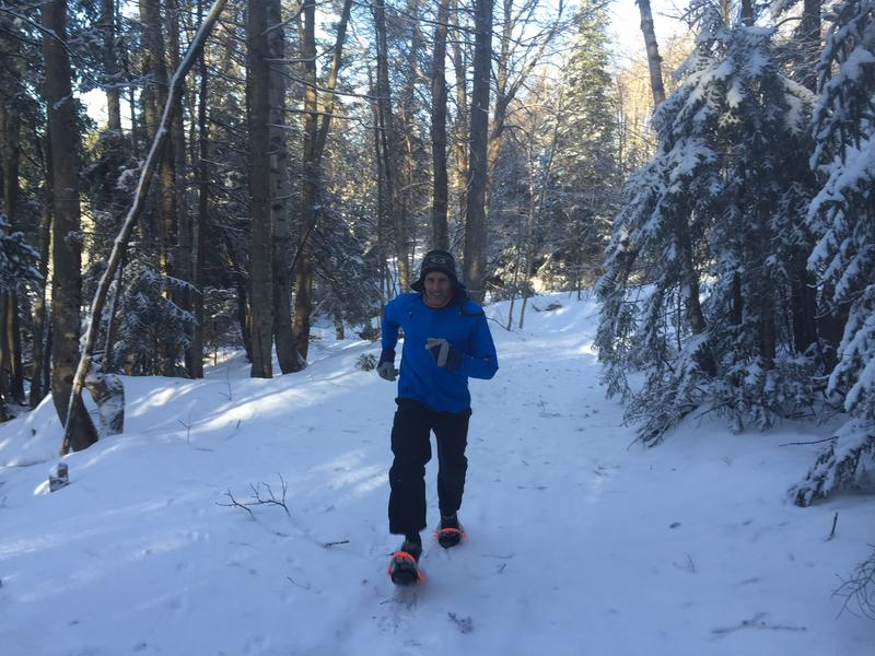 Tim Van Orden of Bennington wears a blue coat and runs on snowshoes through some snowy trees.