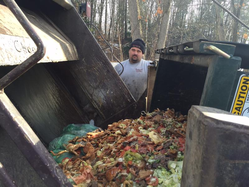 Paul LaFlame of Goodenough Rubbish Removal empties a bin of food scraps while making a stop in Brattleboro.