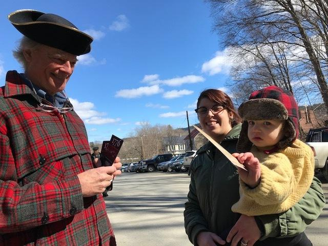 Ham Gillett, who plays John Dickinson in the play 1776, hands out cards with inspiring quotes about democracy, outside the Windsor town meeting.