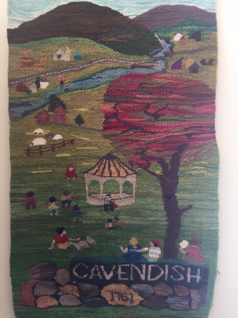 The Cavendish community tapestry which shows a river, tree, gazebo and townspeople and says Cavendish 1761.