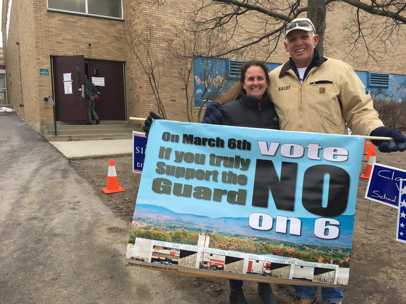 Julie Richards and Scott Baldwin of Burlington hold a sign urging voters to reject a ballot item that seeks to stop the basing of F-35s in Burlington