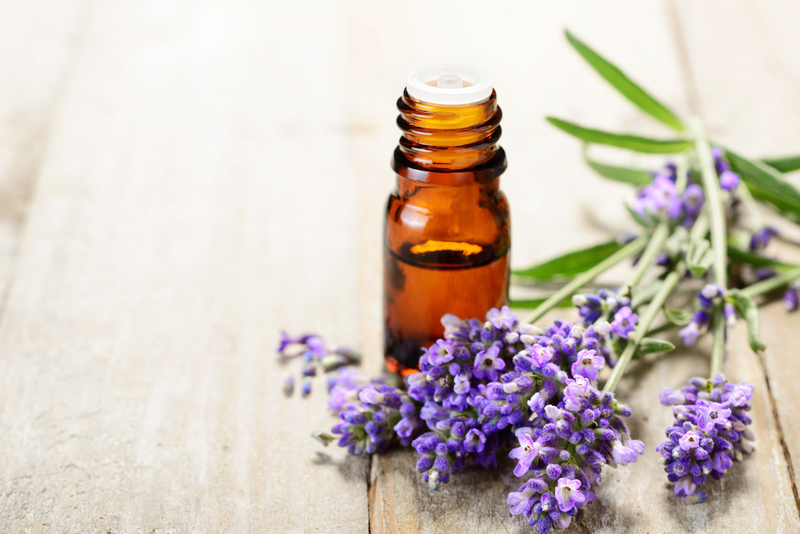An essential oil bottle next to lavender flowers laying down on a surface.