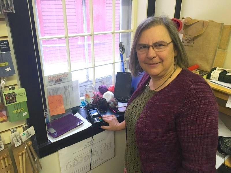 "Lee Youngman, owner of ""Yarn"" in downtown Montpelier, stands next to her shop's credit card terminal. Youngman was told she'd have to pay $8,000 to cancel the lease agreement she signed with a company that leases credit card equipment."