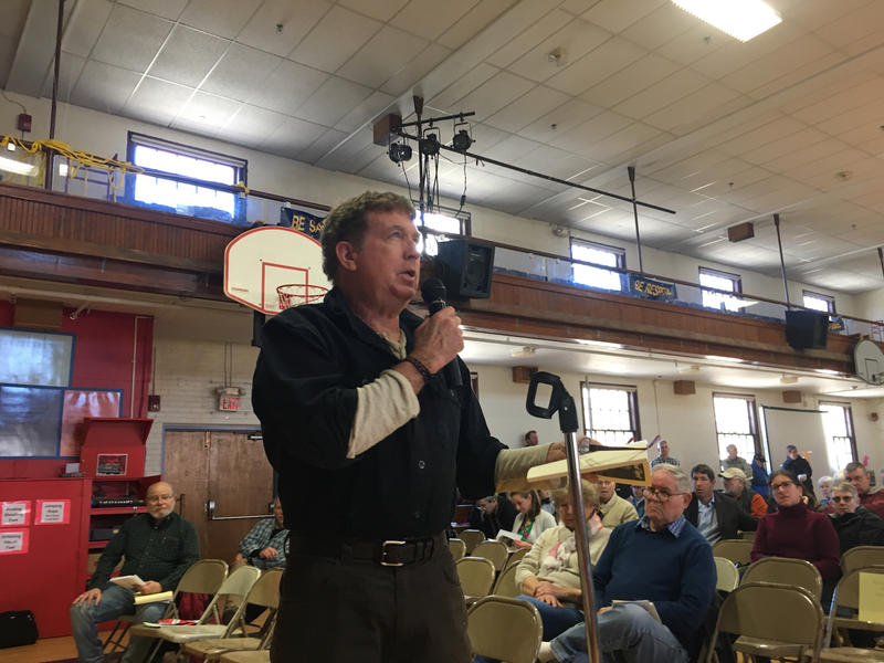 Michael Roche, of Waterbury Center, urged fellow residents at town meeting Tuesday to consider higher pay for town officers. The meeting was in a gym.