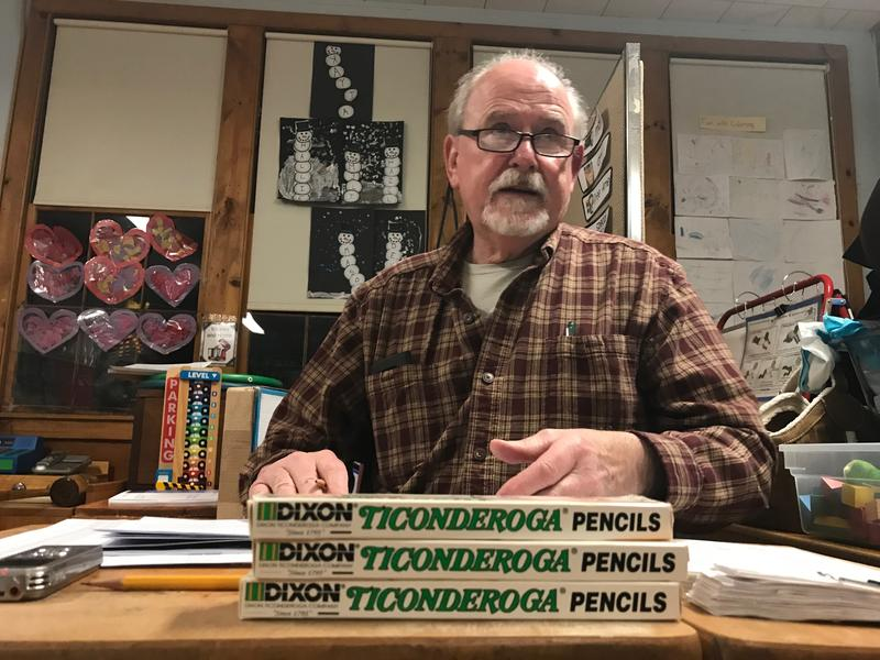 Bill Basso, Mount Tabor town clerk, sits at a desk with three boxes of Ticonderoga pencils in front of him.