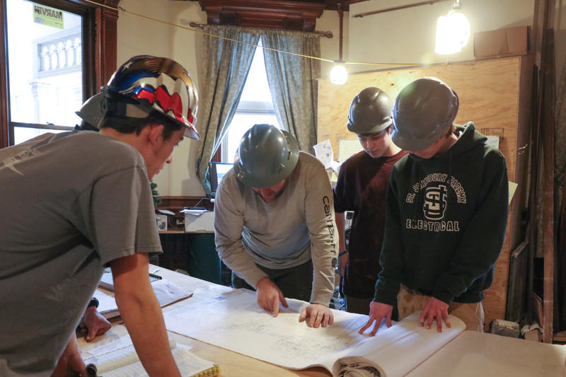 St. Johnsbury Academy electrical program students gather around a table at the Brantview dorm.