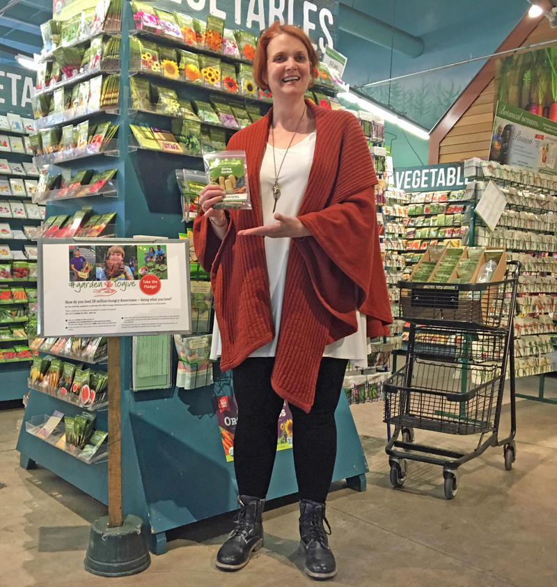 Claudia Marshall holds a bundle of 'Giving Garden' seed packets from High Mowing Organic Seeds, at the Gardener's Supply store in Burlington.