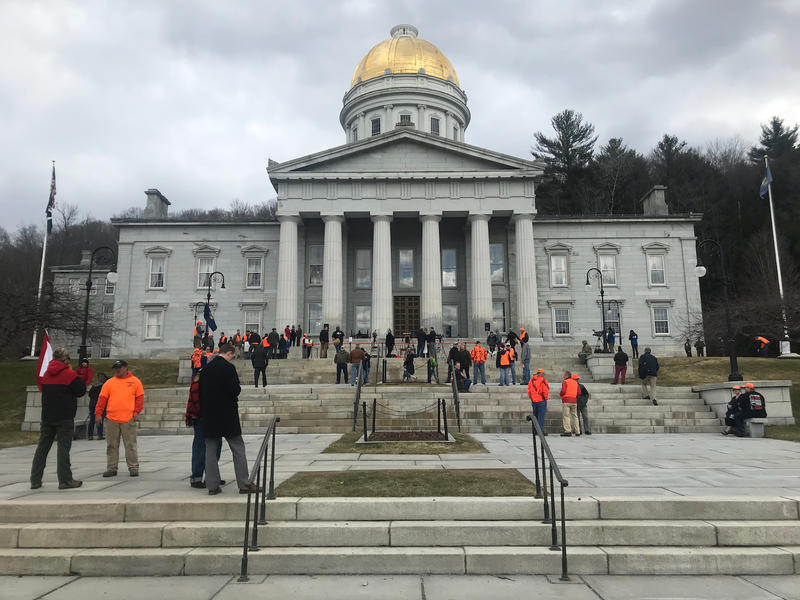 The front of the Vermont Statehouse with people standing around.